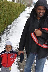 Dagim Addisu, 2, goes for a walk in the snow with his dad, Biniam. STAFF/2016