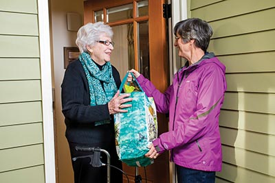 Northeast Village PDX volunteer Julie Granger delivers groceries to Hollywood resident and Northeast Village PDX member Jean Powers. Northeast Village PDX is a nonprofit, grassroots organization that uses trained, background-checked volunteers to provide services that can help keep senior members in their homes for as long as possible. COURTESY NORTHEAST VILLAGE PDX
