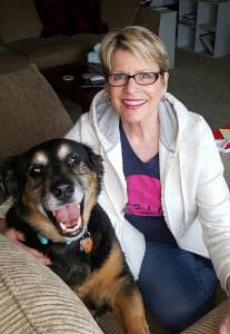 """Former hairdresser Sue Wade said she has learned more about caring for dogs since opening her self-service dog wash in 2011. She poses with Buddy, her nine-year-old Australian Shepherd mix rescue—""""The best dog ever,"""" says Wade. COURTESY DENNIS WADE"""