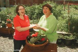 Kirsten Wageman, left, and Judy Alley share a moment in the SnowCap garden.  COURTESY LEEANN GAUTHIER, STUDIO GAUTHIER