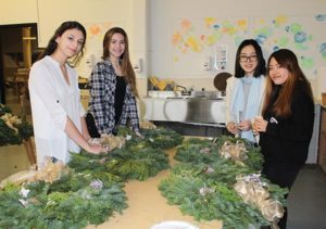 PCS students, from left, Alana Garrett, Megan Roth, Anissa Chak and Giang Huynh put finishing touches on holiday wreaths sold during a 2016 fundraiser. COURTESY GRACE DUGGER