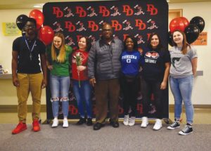 David Douglas High School Athletic Director Greg Carradine, center, celebrates with students who signed letters of intent to play sports at the college level. They are, from left, Ume Bandas, football, College of the Siskiyous, Weed, California; Sydney Wallstrum, softball, Highline College, Des Moines, Washington; Shalea Dailey, softball, Clackamas Community College; Lyndra Banks, cheer, acrobatics and stunt, Glenville State College, Glenville, West Virginia; Jennifer Oliva-Lopez, softball, Clackamas Community College; and Makayla Combs, softball, Chemeketa Community College. COURTESY STEPHANIE MATTHEWS, DDHS ATHLETIC DEPARTMENT