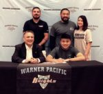 Warner Pacific Athletic Director and Wrestling Coach Frank Johnson signs letter of intent with Anthony Cha as family members look on. COURTESY STEPHANIE MATTHEWS, DDHS ATHLETIC DEPARMENT