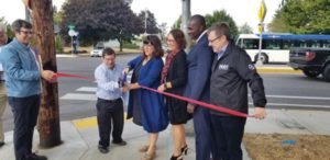 Portland Bureau of Transportation Communications and Public Involvement Director John Brady, from left, holds the ribbon for former Commissioner Steve Novick and Commissioner Eudaly to cut at the unveiling of a new flashing crossing signal on Northeast 122nd Avenue at Stanton Street. Also holding the ribbon are Multnomah County Commissioner Jessica Vega Pederson, TriMet Chief Operating Officer Maurice Henderson and PBOT Interim Director Chris Warner. STAFF/2018