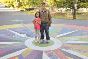 Bob Cole and his great-granddaughter Kinley pose on a street mural at the intersection of Northeast Skidmore Street and 110th Avenue. Created last summer, a depiction of a compass was chosen by the community over two alternatives because of an online poll. All three designs had the focused, circular patterns and many colors. STAFF/2018