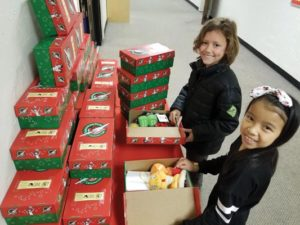 Columbia Christian School students cheerfully pack boxes with personal care items, school supplies, toys, crafts and activities. These care packages will be donated to Samaritan's Purse, a charity that will distribute the boxes to children ages 2 to 14 this holiday season. COURTESY CCS