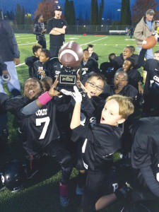 Parkrose Colts hoist the Portland Youth Football City Championship trophy. COURTESY Brian Johnson