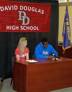 Kennedy Allen, a DDHS senior looks on as classmate Osa Odighizuwa pens his signature to an NCAA Letter of Intent committing to play football at UCLA. Allen made a similar commitment to the track team at UNLV. COURTESY DAVID DOUGLAS SCHOOL DISTRICT
