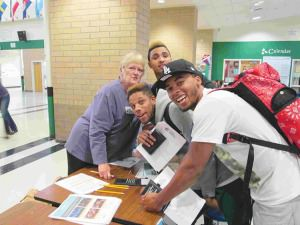 Parkrose School District board of education member MaryLu Baetkey poses with, from back to front, Parkrose High School Seniors Jon Boland, Tyrell Lee and A.J. Blake at Pacific NW Federal Credit Union's Financial Reality Fair. Baetkey volunteered at a booth selling simulated entertainment options to kids. COURTESY JULIA ANDERSON